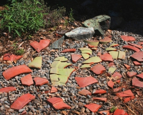 Broken terracotta clay pots can still be used near the hose.