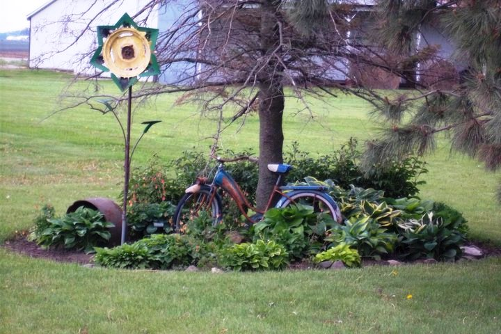 This bike was mine as a young girl and my husband made sunflower from old machinery parts, and the old kettle is from a dear older neighbor.