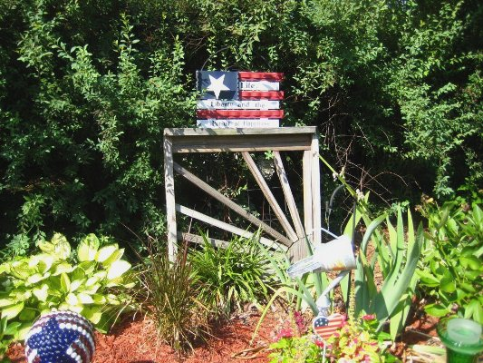 An old gate creates a background for more flea market and junky garden art.
