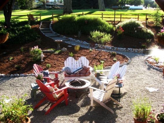 A gravel patio features Adirondack chairs and a fire pit.