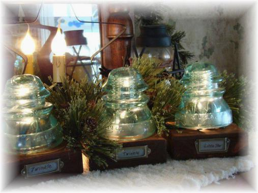 "Jeanne Sammons advises, ""Never pass up those 'blue insulators' at flea markets! Seeing Sue use them in a birdbath reminded me of this winter project...3 blocks of wood, strand of mini-lights, 3 metal label thingy's and some faux greenery behind it all...'Twinkle, Twinkle, Little Star!'"""