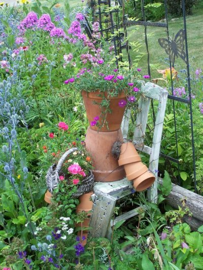 Donna Anderson's pot lady, sits on a worn wooden chair surrounded by soft flowers.