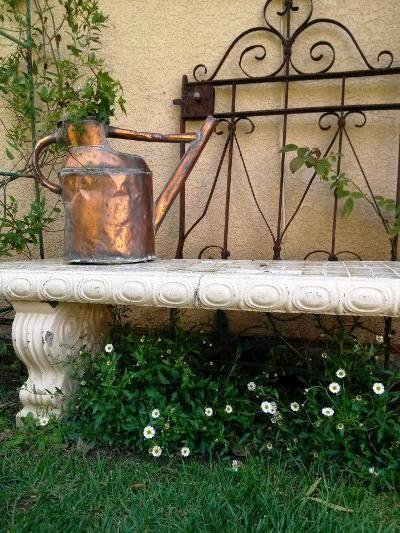A treasured copper watering can, a stone-like concrete bench and an ornate gate combine in this vignette.  Santa Barbara daisy grows below.