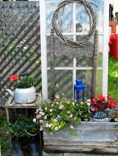 An chippy French door and old crates with flowers