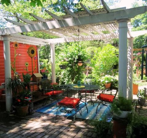 A shady seating area has a pop of orange