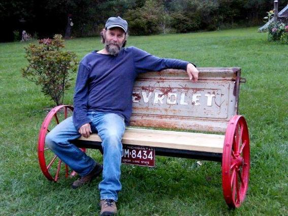 Here is my friend, Larry,  maker of this wagon wheel tailgate bench...