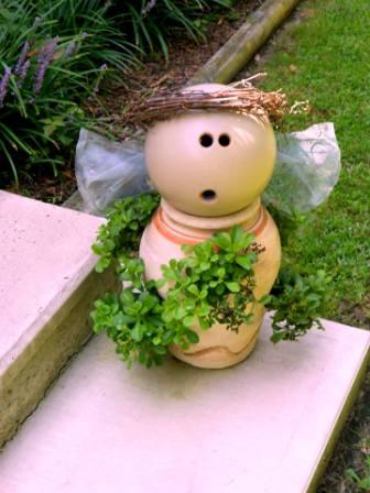 """Mary Everett says, """"Here's my garden angel, I made today. I realized the driftwood piece found on the beach was the perfect shape for wings. Found a board for the body in hubby's scrap pile, and the pots were from yard sales. I can't resist clay pots!"""""""