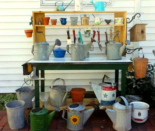 "Nancy Carter says, ""My favorite project for this year was my potting bench. We bought a porcelain topped table at half price at the end of an estate sale and added the shelves and hardware cloth."""