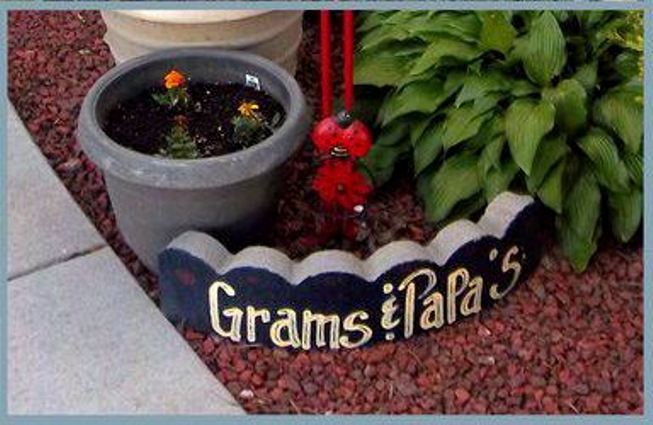 Nancy K. Meyer is a proud Grandma and painted this sign on a cement tree ring piece.