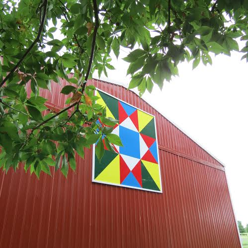 "This huge  8'x8'  ""quilt"" was made from 3 sections of aluminum, and then painted and hung by its creator, Diana's son Mark, and another son Jeff, along with 3 grandsons."