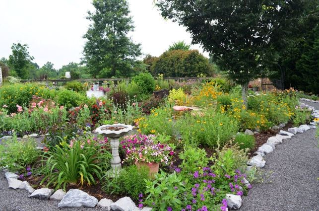 A birdbath accents the bed and mulch keeps the weeds under control.  Christy pops containers in as they bloom.