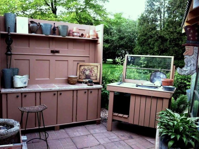 Ann and Mike Elias worked on this potting bench and what's inspiring is that the total cost so far is under $50! Hooks and a tile top were added. The doors on the back and fish stand were free. They used a gallon of 'oops' paint from Home Depot and only had to purchase the shelf and side boards at full cost. Tile was found for .50 cents each and the doors on the side were $2, both at the Habitat for Humanity Restore.