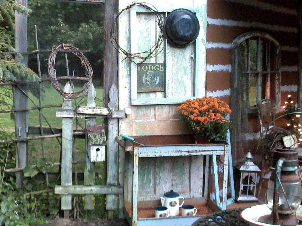 """Dean McCall says, """"Fall is tryin' to creep in at our house; found some Mums beside my """"faux"""" Cabin Porch"""" on my makeshift Potting bench, by my little pond already!"""""""