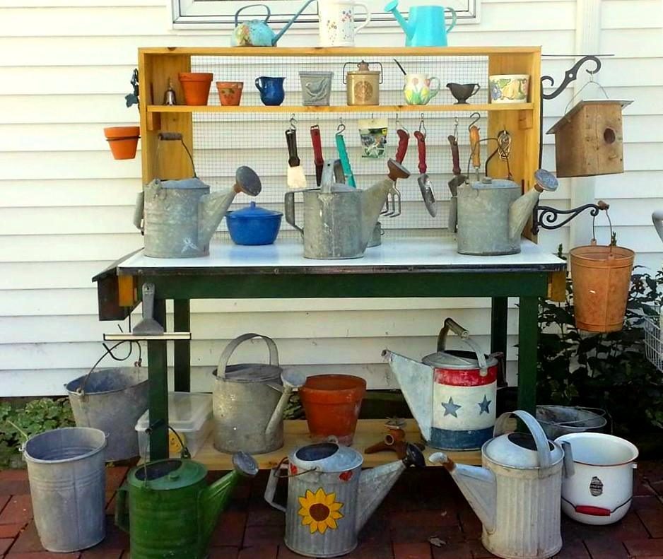 """Nancy Carter says, """"My favorite project for this year was my potting bench. I found a nice sturdy table with an enamel top. The top had been painted (very badly). I stripped it back to the enamel and we added a shelf at the bottom and shelves at the top. I put 1"""" hardware cloth behind the upper shelves to hang tools and hung an old mailbox onto the side for storage and a couple of brackets. I am really happy with the way it turned out."""""""