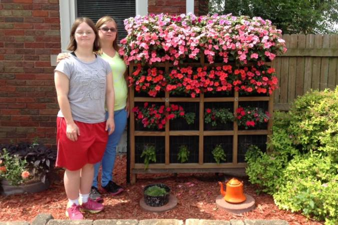Nancy's daughter and granddaughter by the planter, now blooming at its peak!