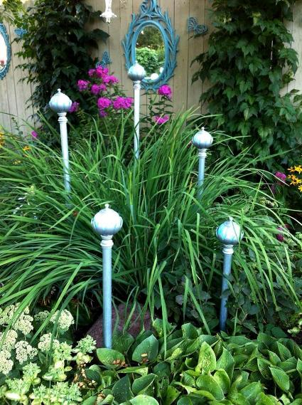 Ann Elias accented her green garden bed with cast off curtain rods she custom spray painted