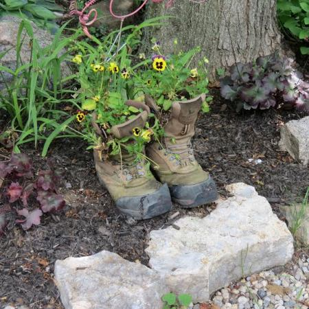 Almost nothing gets thrown away that can hold some dirt for a plant, such as these worn boots that sit near the entrance way
